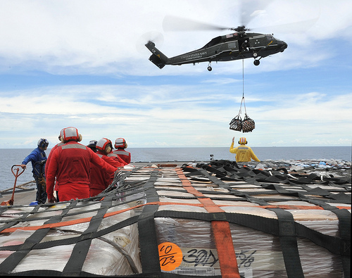 Helicopter moves supplies to USS Blue Ridge from USNS Rappahannock while enroute to Japan.